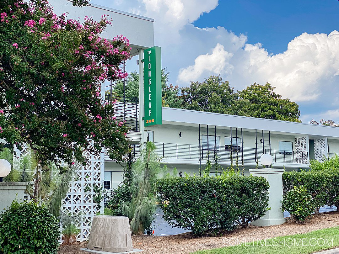 Exterior of a hotel with a Longleaf Hotel sign in green, vertically, and blue skies and green landscaping.