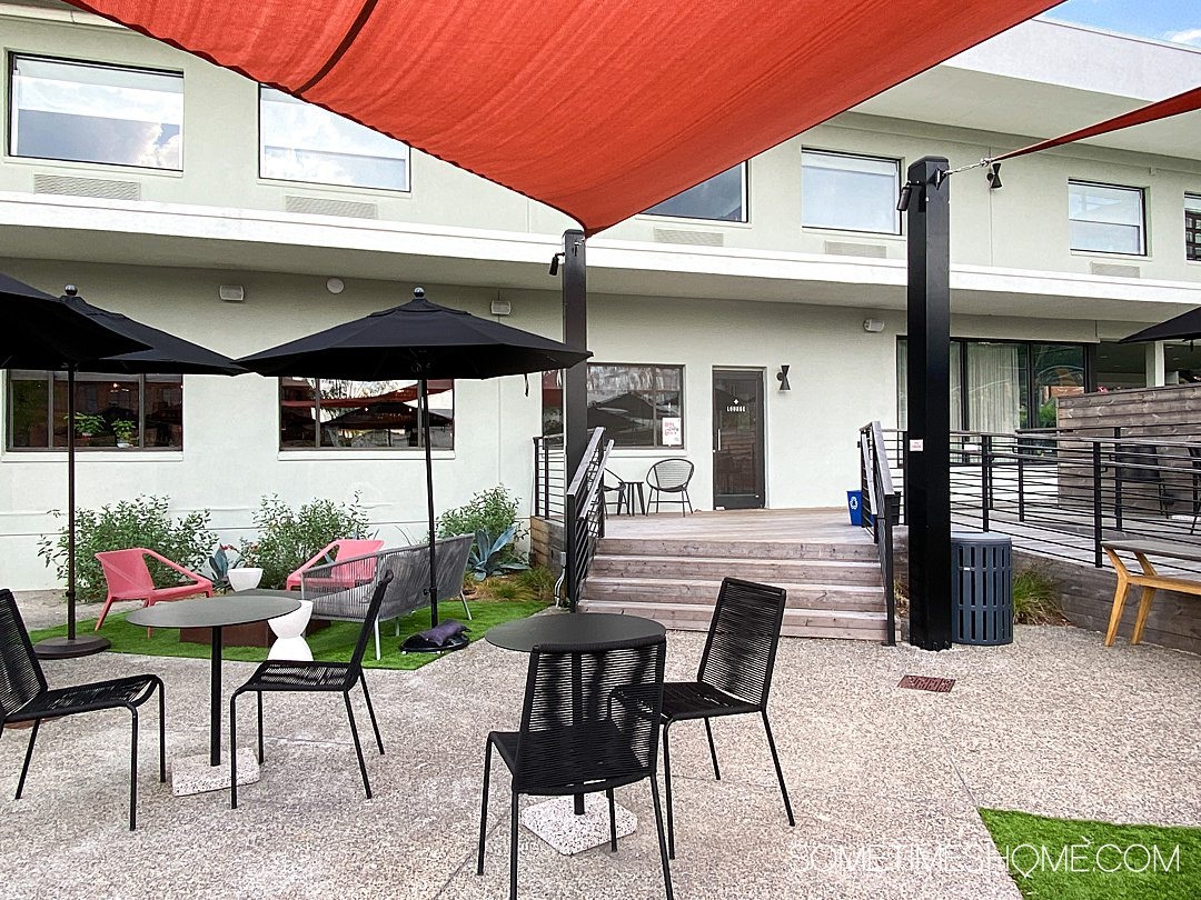 Outdoor area of the Longleaf Hotel, with red-orange shade awnings, black umbrellas and seating areas.