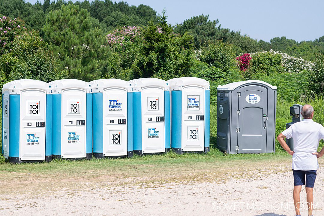 Portable toilets by the sunflower field in North Carolina, with trees behind it.