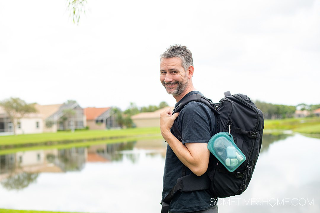 """Man with a travel backpack on and a Stasher """"Go"""" bag with a carabiner attached."""