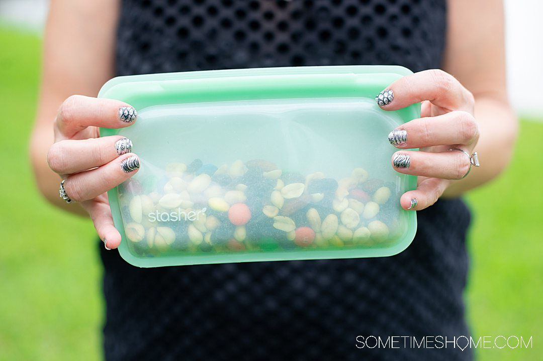 Woman's hands holding a green snack size Stasher bag, a Ziploc bag alternative.